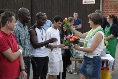 (Foto: WLL) Regina Selhorst (Präsidentin WLLV) überreicht Nelli Foumba (Sprecher der JoG NRW) und weiteren Flüchtlingen eine Rose als Willkommensgeschenk.
