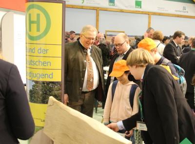 (Foto: WLL) Gerd Wesselmann (WGZ-Bank) wird von Sebastian Jakobs (Vorsitzender WLL) über den Landjugend-Stand geführt.
